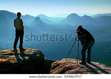 Hiker and photo enthusiast stay with tripod on cliff and thinking. Dreamy fogy landscape, blue misty sunrise in a beautiful valley below