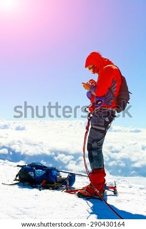 hiker at summit with backpacks calling on the phone. the sunrise in the mountains. Mount Kazbek, Georgia, Caucasus. - stock photo