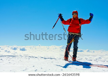 hiker at the top of a pass with backpacks meeting the sunrise in the mountains. Mount Kazbek, Georgia, Caucasus. - stock photo