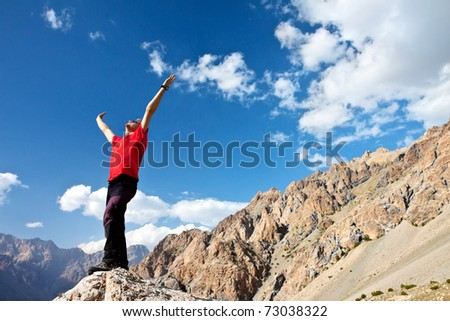 hiker at the top of a rock with his hands up enjoy sunny day - stock photo
