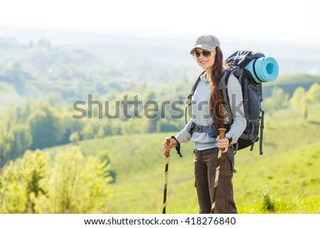 Hiker backpacker girl enjoying journey in mountains. Young smiling woman with backpack traveling in countryside - stock photo