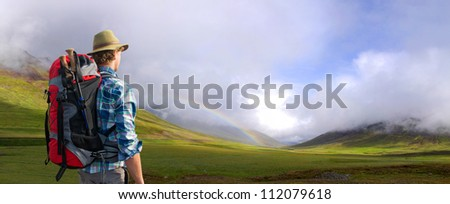 Hiker being overwhelmed and in awe of the Icelandic landscape that surrounds him. A rainbow appearing in a shower from the low clouds over the lush green meadows - stock photo