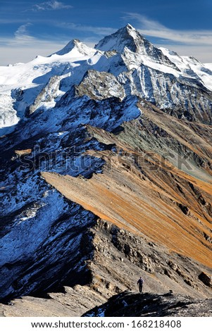 Hiker below Dent Blanche, Swiss Alps - stock photo