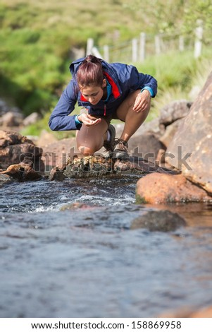 Hiker bending to take a drink from the stream in the countryside - stock photo