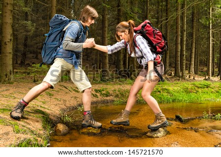 Hiker boy help trekking girl crossing the creek - stock photo