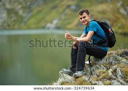 Hiker boy with backpack by the lake in the mountains