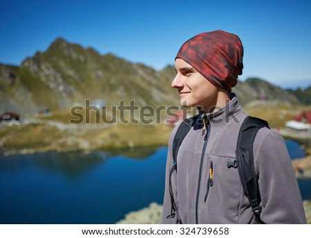 Hiker boy with backpack by the lake in the mountains - stock photo