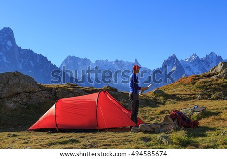 Hiker checking a map at his red tent in the mountains near Chamonix, France.