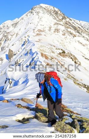 Hiker climbs on snowy mountain ridge in sunny day - stock photo