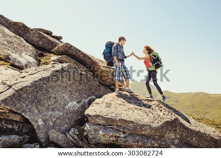 Hiker couple helps each other to climb on the rock in mountains - stock photo