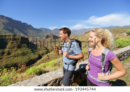 Hiker couple hiking on Gran Canaria. Romantic hikers enjoying hike in beautiful mountain forest landscape. Blonde woman hiker and Caucasian man on Gran Canaria, Canary Islands, Spain. - stock photo