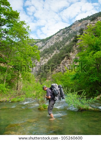Hiker crosses a river at the ford - stock photo