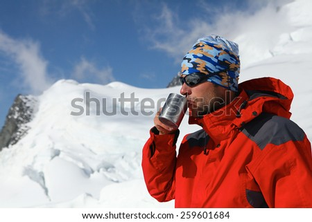 hiker drink coffee or tea in beautiful Himalaya mountains on hiking trip, Nepal. Active person resting outdoors in winter white nature - stock photo