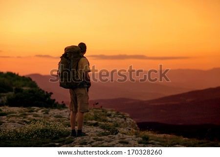 hiker enjoying sunrise from top of a mountain - stock photo