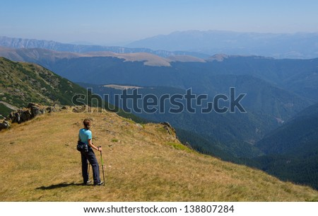 Hiker enjoying the view in the mountains, Romania - stock photo