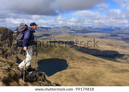 Hiker enjoying the view in the Scottish highlands. - stock photo