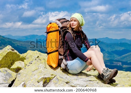 Hiker enjoying valley view from top of a mountain  - stock photo