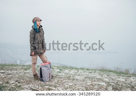 Hiker girl standing on peak of mountain with backpack and looking somewhere
