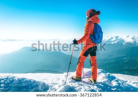 Hiker happy woman trekking on the snow in a snowy mountain in wi - stock photo