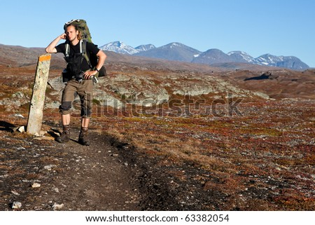 Hiker have a break on a way sign - stock photo