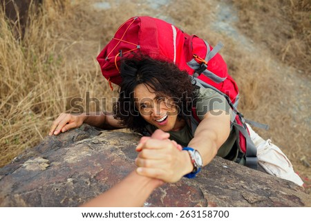 Hiker helping his friend to climb the rock - stock photo