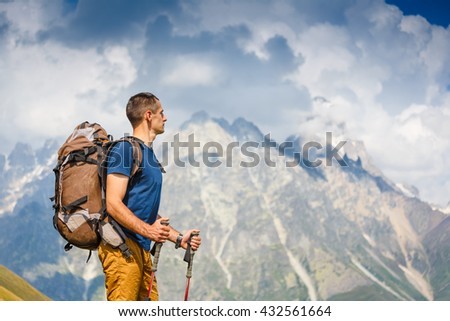 Hiker hiking with backpack looking at mountain view - stock photo