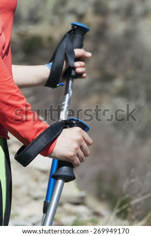 Hiker holding hiking poles with straps, close-up - stock photo