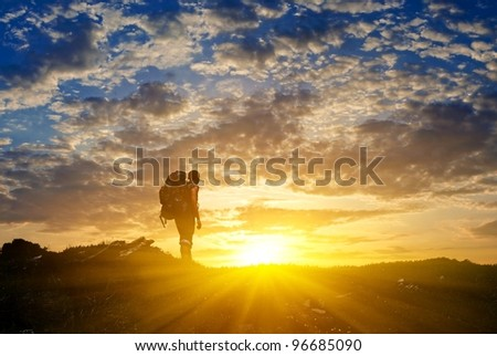 hiker in a mountains at the sunset - stock photo