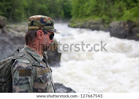 Hiker in camouflage clothing on the rocky shore of a Kema river. Russia. Primorskiy kray.