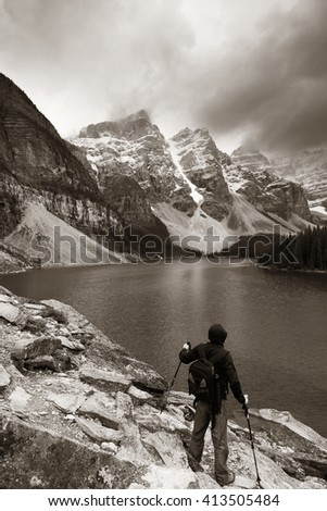 Hiker in Moraine Lake with snow capped mountain of Banff National Park in Canada - stock photo