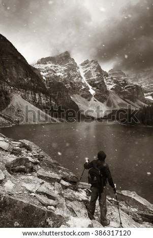 Hiker in Moraine Lake with snow capped mountain of Banff National Park in Canada in a snowing day - stock photo