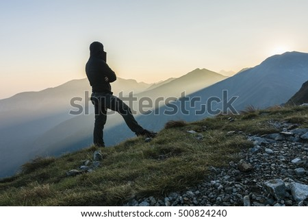 Hiker in the mountains watching the mountains in the morning.