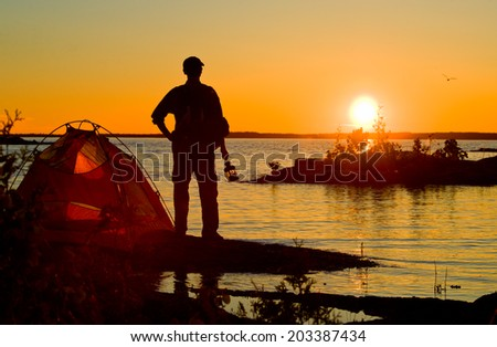 Hiker in the Sunrise with Tent  - stock photo