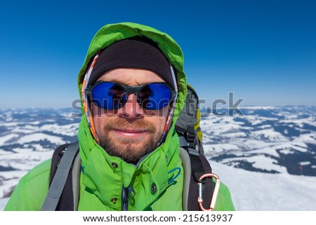 Hiker in winter mountains during sunny day