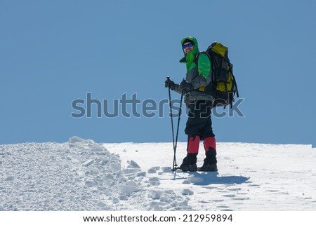 Hiker in winter mountains on sunny day