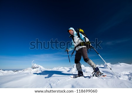 Hiker in winter mountains snowshoeing - stock photo