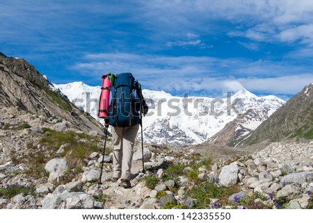 Hiker is approaching wall covered with snow in Caucasus mountains  in Bezengi region, Kabardino-Balkaria, Russia