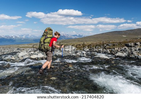 Hiker is crossing the river in sweden - stock photo