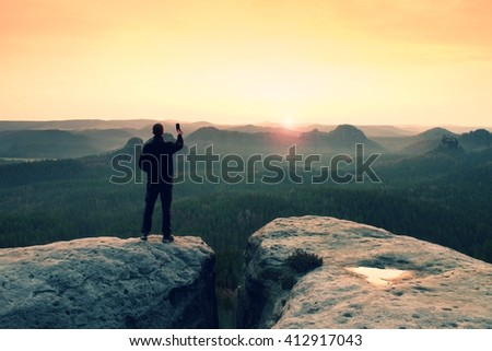 Hiker is taking photo by smart phone on the peak of mountain at sunrise.