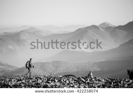 Hiker is walking on the rocky mountain on backpacking trip. Man is wearing jacket and backpack on. Beautiful mountains on background. Ecotourism and healthy lifestyle concept. black and white - stock photo