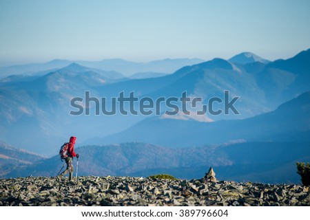 Hiker is walking on the rocky mountain on backpacking trip. Man is wearing red jacket and backpack on. Beautiful mountains on background. Ecotourism and healthy lifestyle concept. Copy space. - stock photo