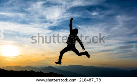 hiker jumps high in the air celebrating success in the sunset