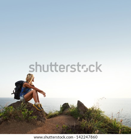 Hiker lady with backpack relaxing on a rock by sea and looking to the horizon - stock photo