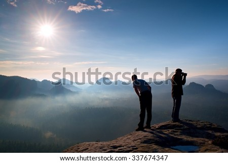 Hiker look down into valley. Photo enthusiast stay on cliff and takes photos. Dreamy fogy landscape, blue misty sunrise in a beautiful valley below
