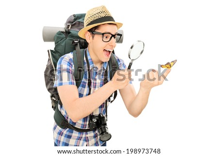 Hiker looking at a butterfly through a magnifier isolated on white background - stock photo