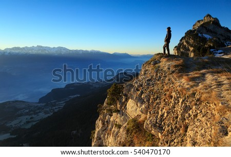 Hiker looking at the rising sun during dawn in the French mountains.