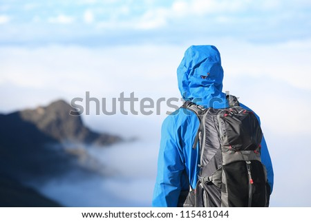 Hiker looking at view in high altitude mountain above the clouds. Mountaineer man enjoying view at summit top in alpine wear with backpack. - stock photo