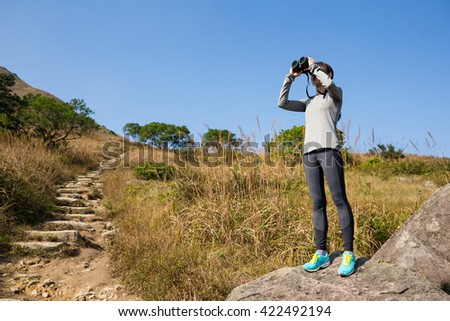 Hiker looking in binoculars enjoying spectacular view on mountain - stock photo