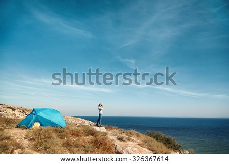 Hiker looking in binoculars enjoying spectacular view on mountain top above the clouds in national park - stock photo