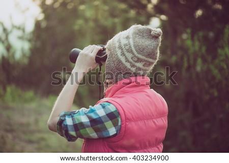 Hiker looking in binoculars enjoying view in forest during hiking trip. - stock photo